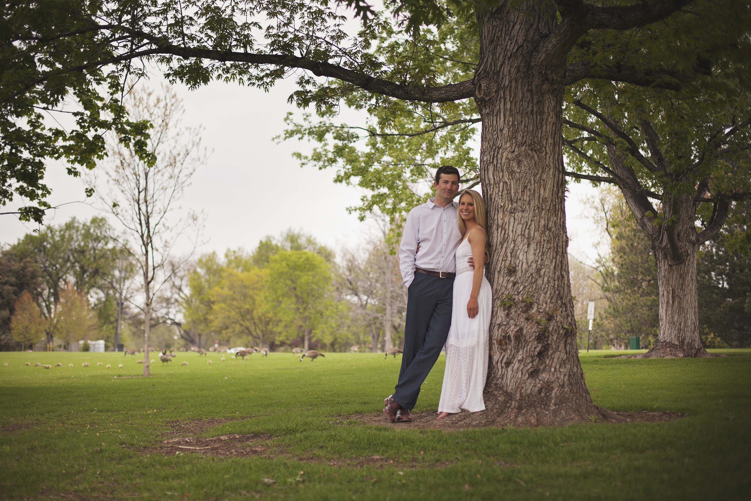 Couple leaning on tree with green grass around them during engagement photo session
