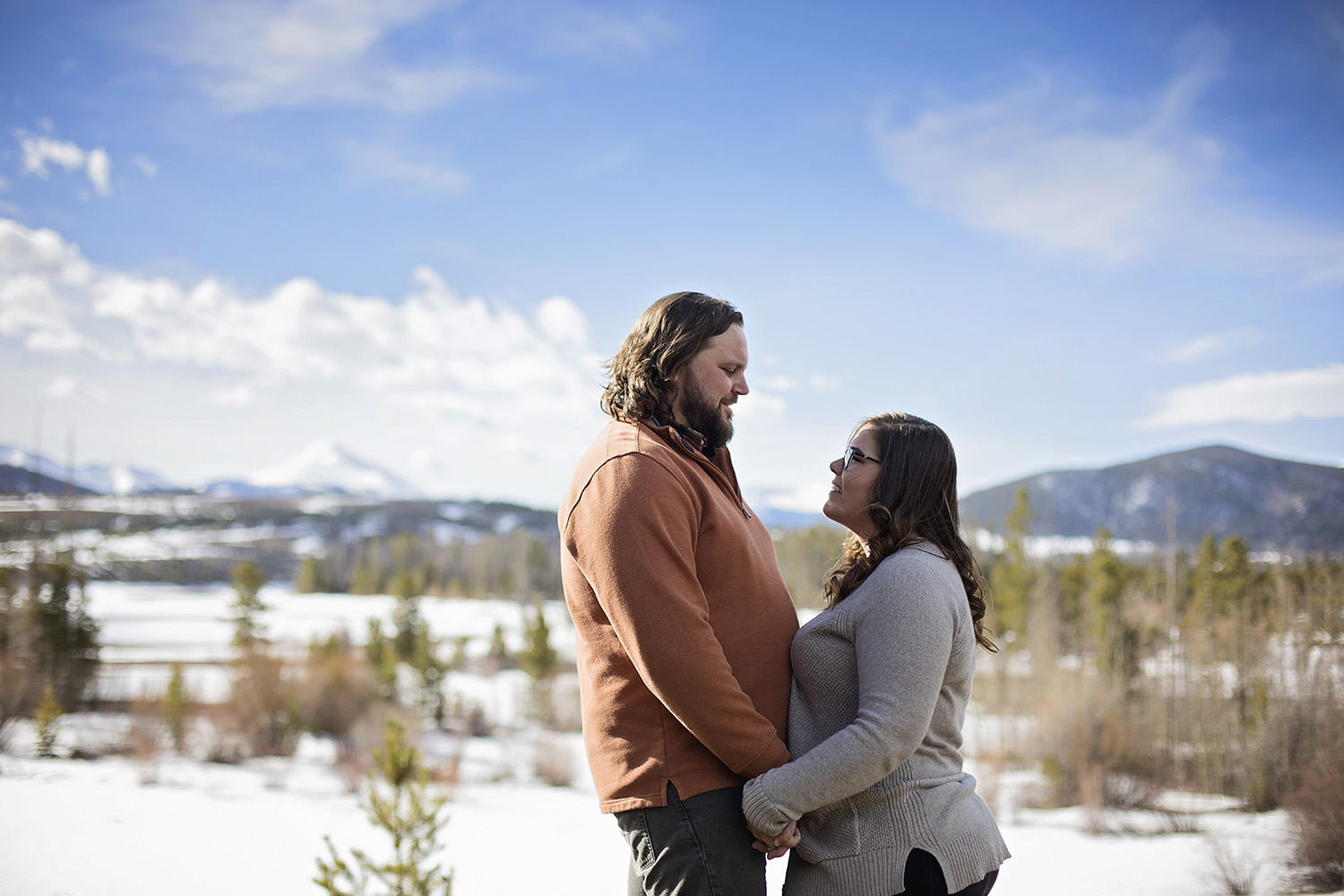Couple holding hands close to each other in the snow with mountains