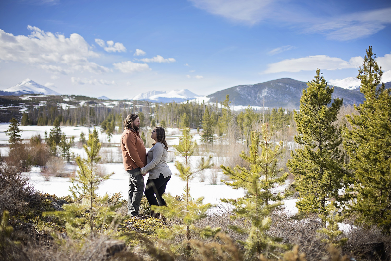 Engaged couple facing each other with bright green line trees around them and mountains behind