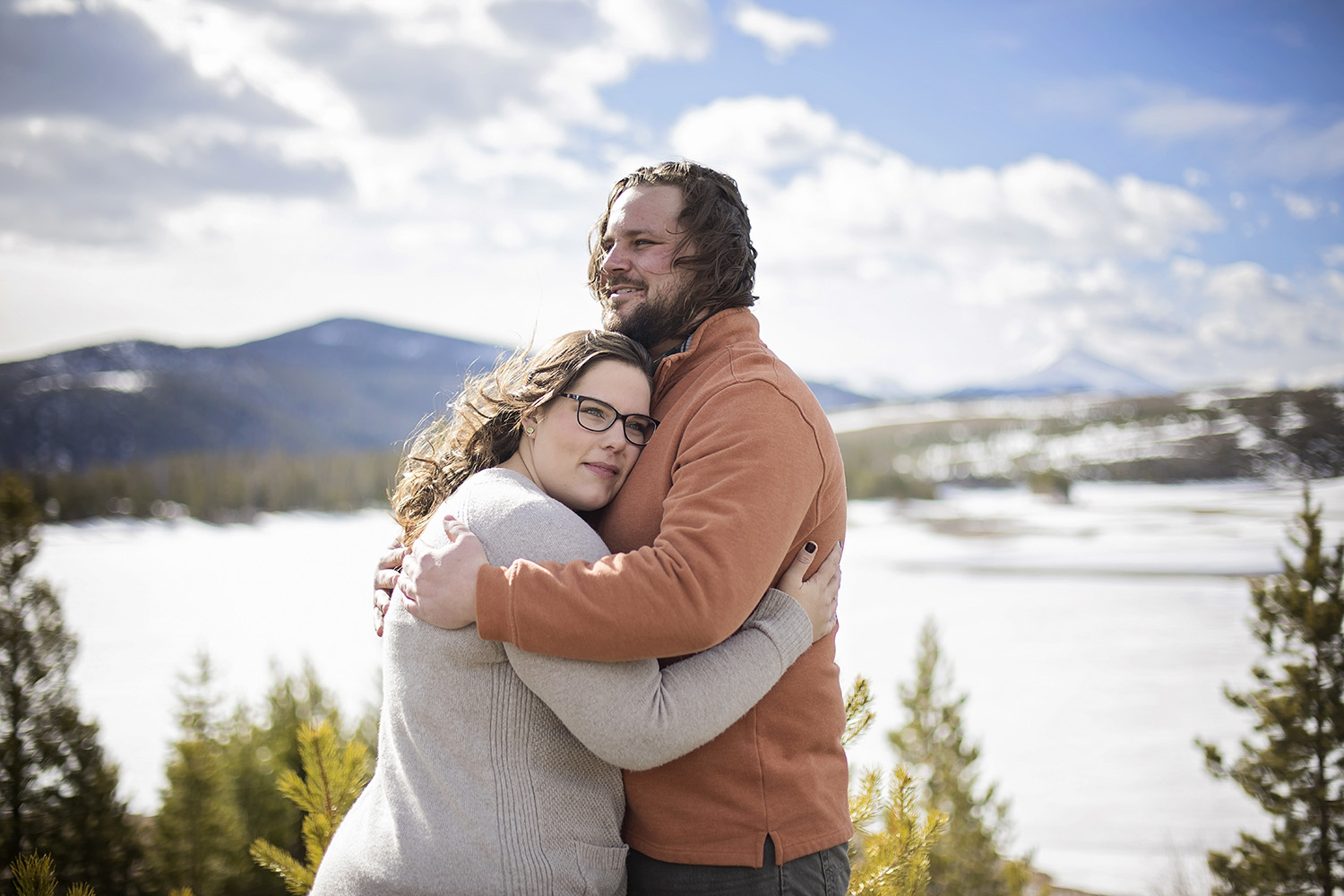 Man hugging his fiancé with snow and mountains behind them