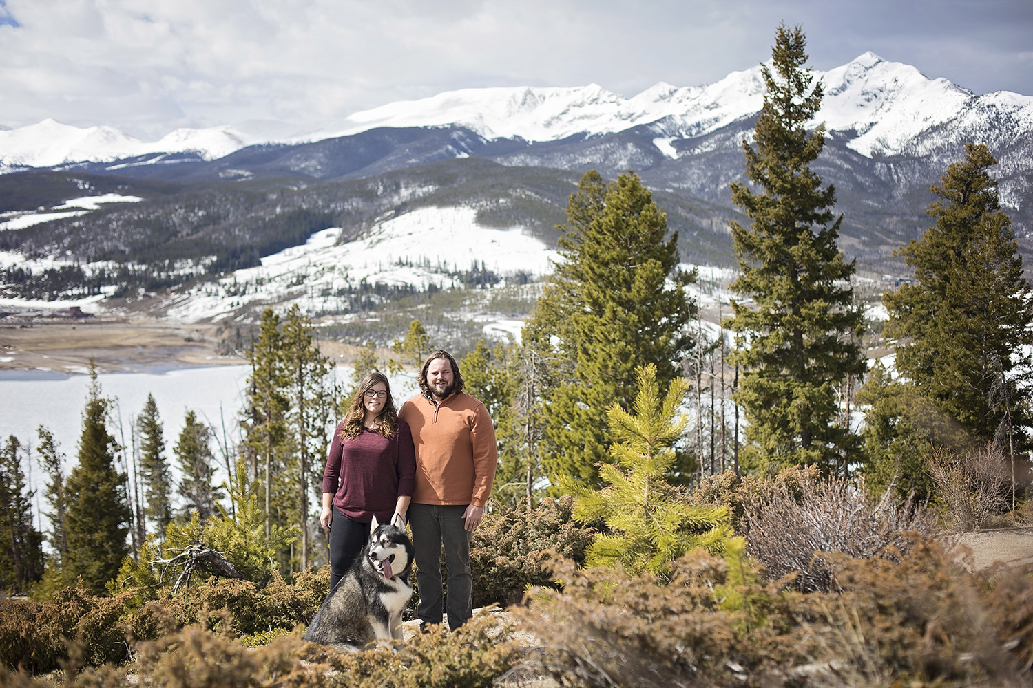 Engaged couple standing with their husky on the shoreline of Dillon Reservoir