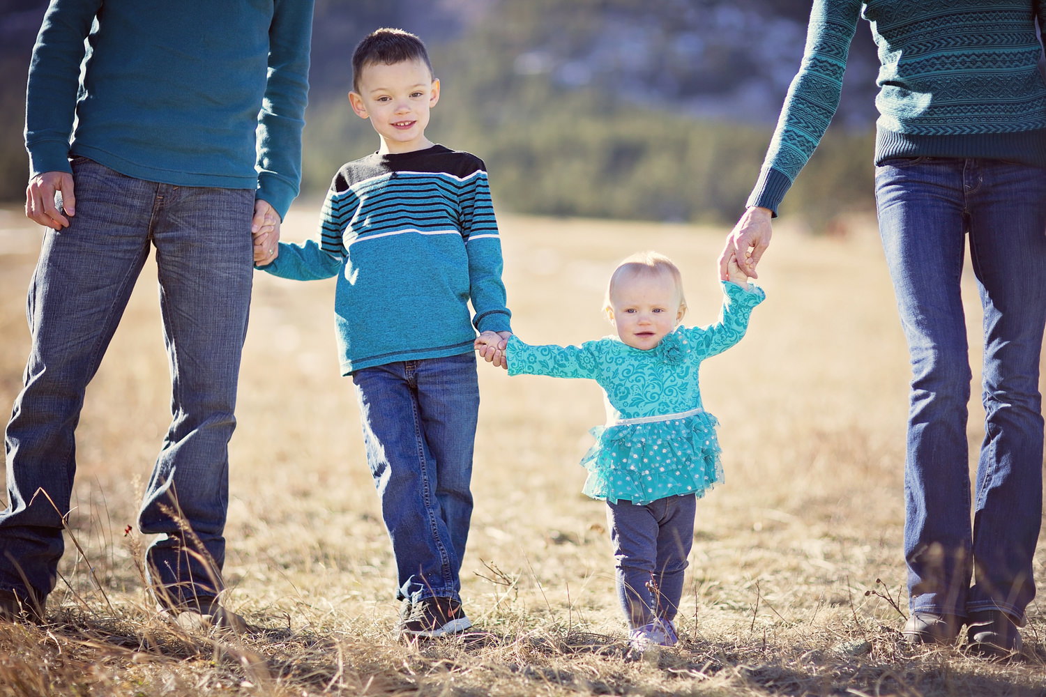 Parents just out of frame holding hands of kids all with coordinated colors