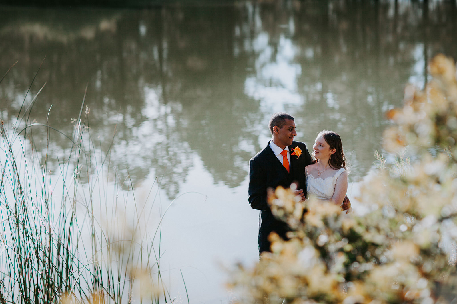 Newlyweds embracing side by side with pine trees reflected in lake behind