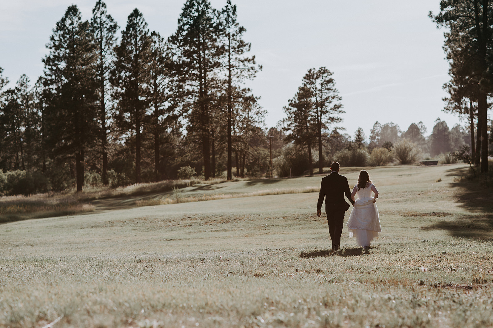 Just married couple walking through meadow with sun peering behind them