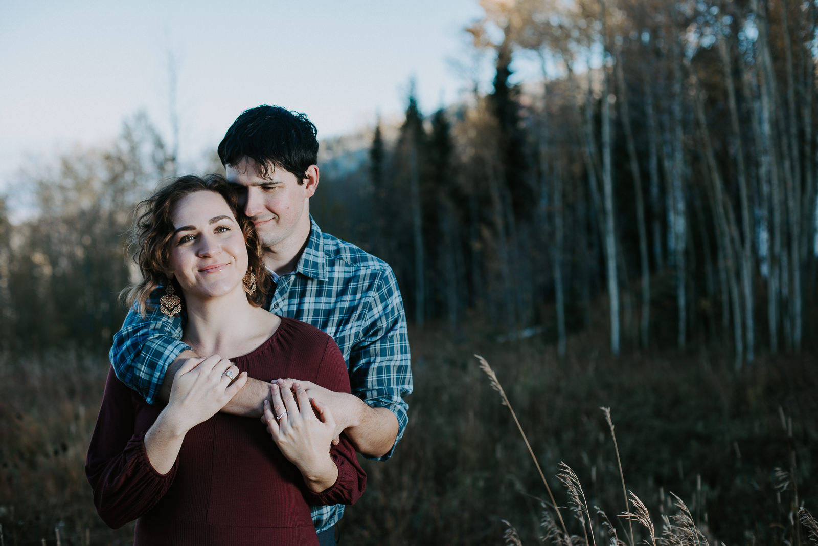 Smiling engaged couple embracing with aspen trees