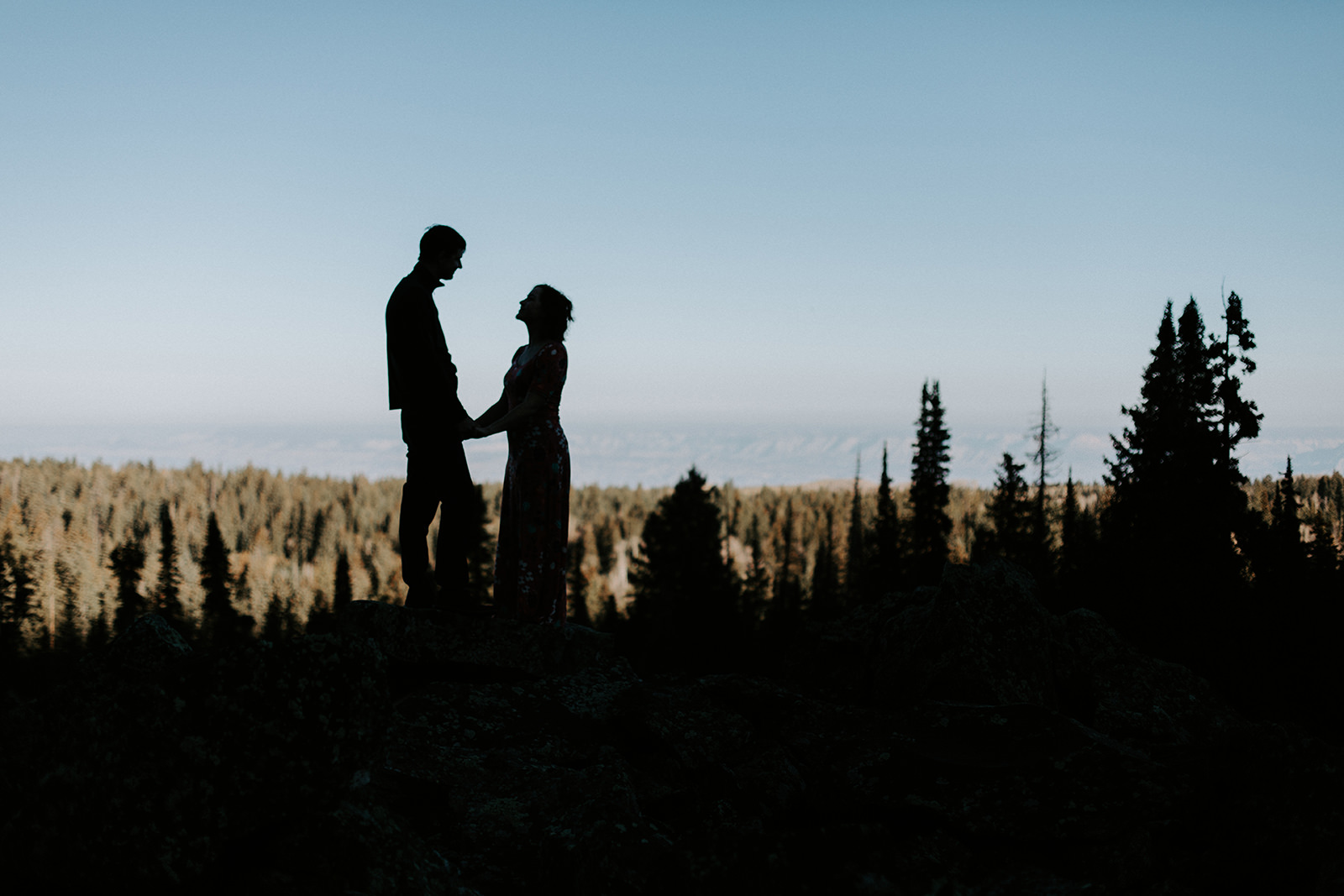 Silhouette of engaged couple with pine trees and sky in the background on Grand Mesa