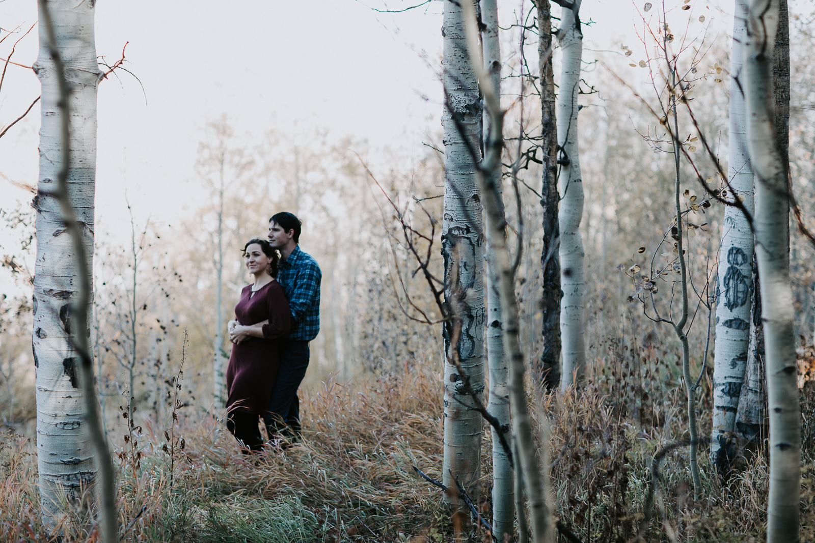 Engagement photograph of couple hugging among aspens and a meadow
