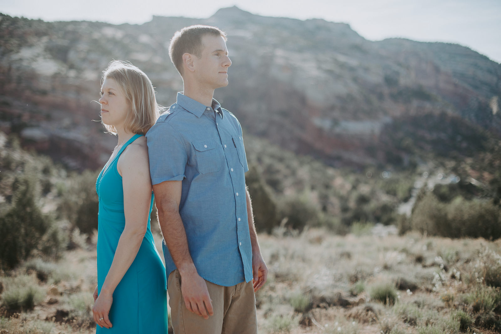 Couple standing back to back in engagement photograph