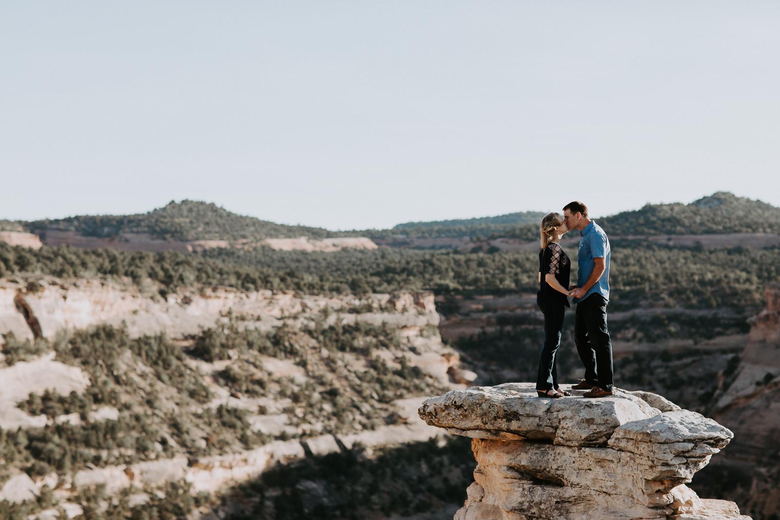 Couple kisses on cliff in the desert