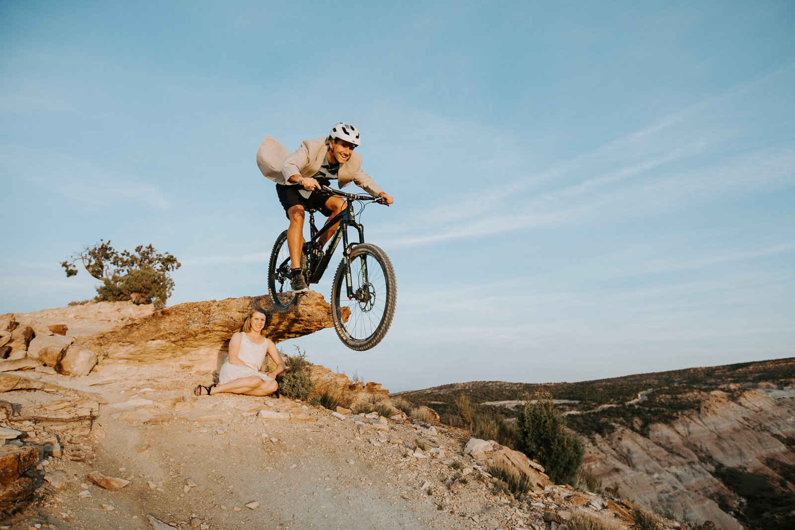 Front view of man jumping his mountain bike over his fiancée at the Lunch Loops during engagement photography session
