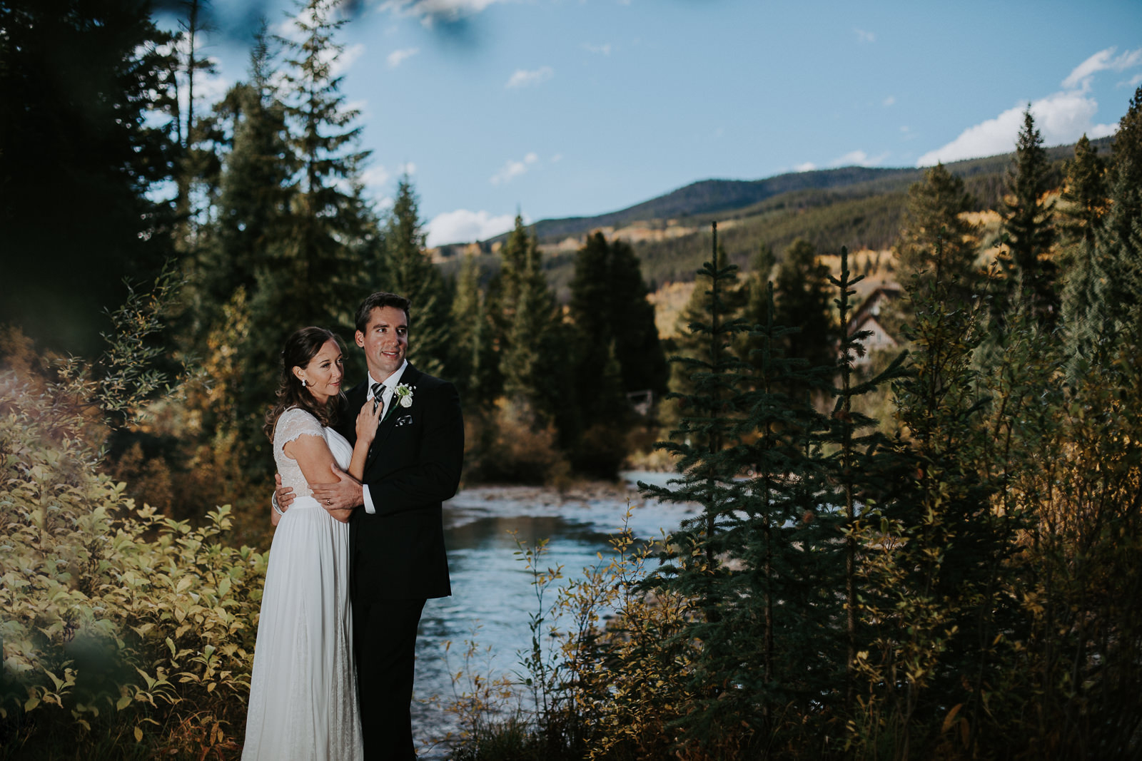 Wedding photography of couple standing along river smiling with a river and mountains behind them