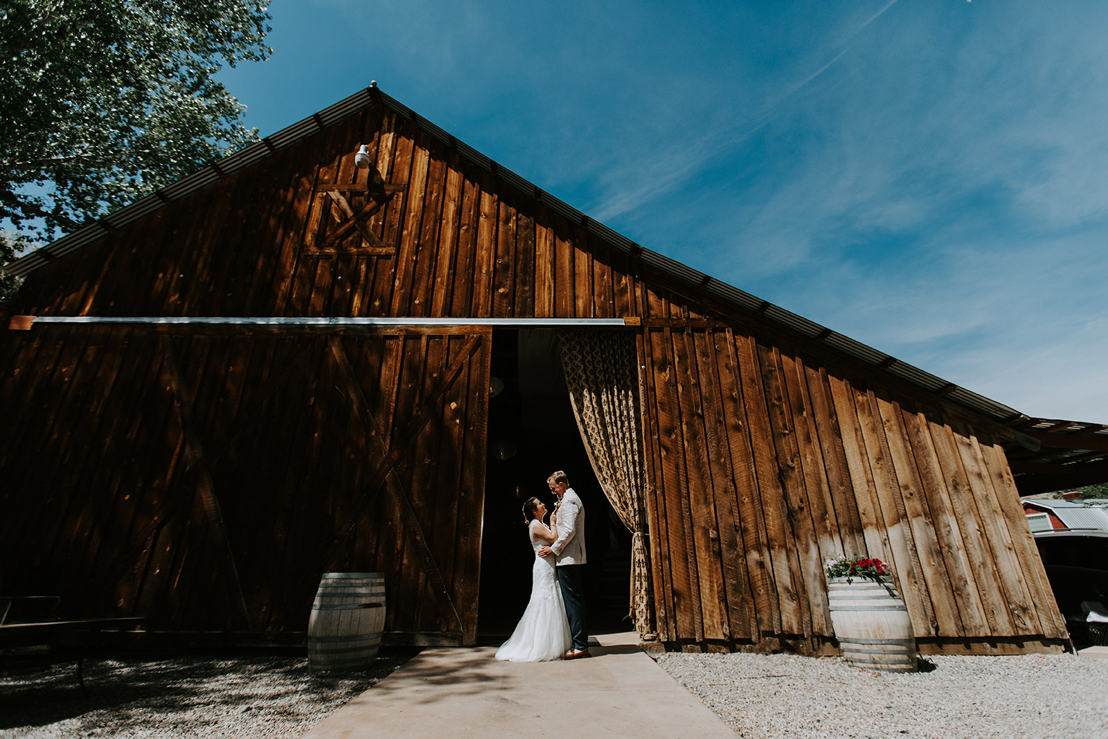 Wedding photograph of bride and groom facing each other in front of barn at Amy's Courtyard