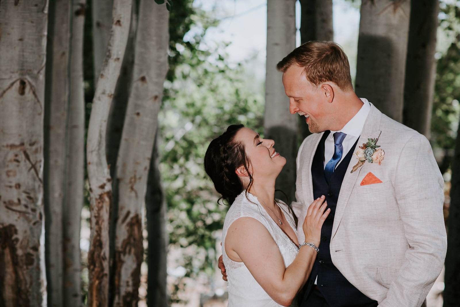 Smiling newlyweds standing close in honest moment during wedding photography session in Palisade, Colorado