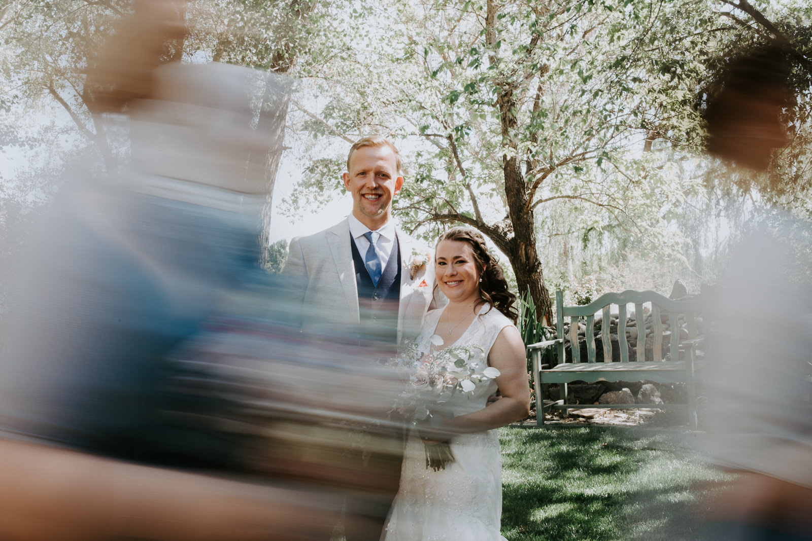 Long exposure of happy couple with wedding party blurred walking by
