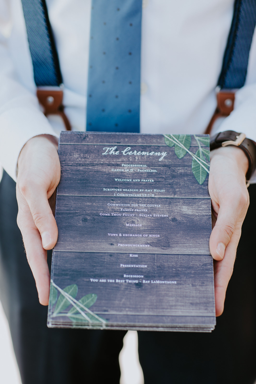 Close up of a wedding program that a groomsman is holding
