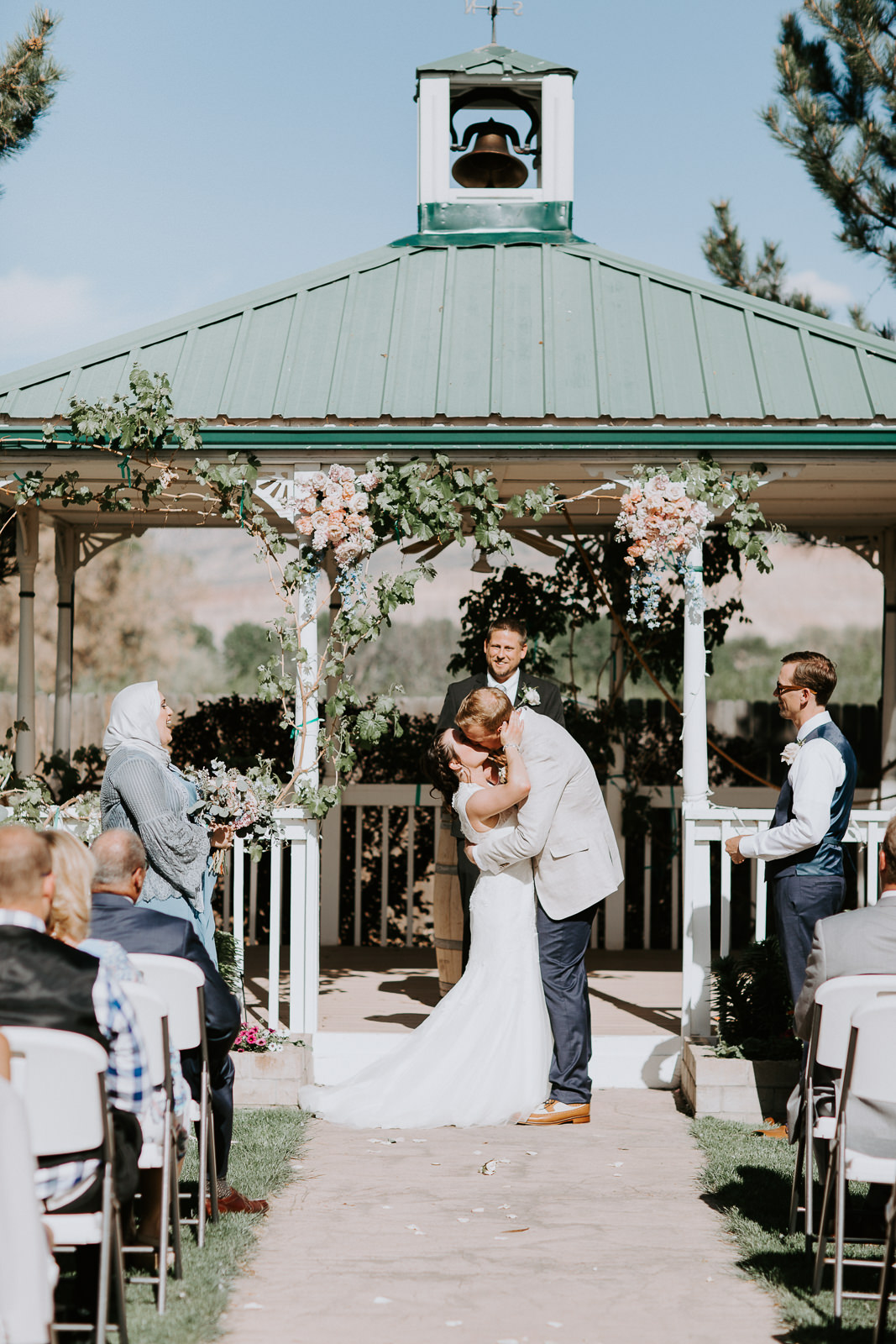 Bride and groom kissing in front of gazebo at end of wedding ceremony in Palisade, Colorado