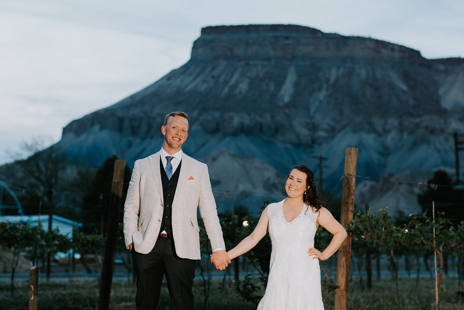 Smiling groom and bride illuminated with Mount Garfield in background near Grand Junction, Colorado