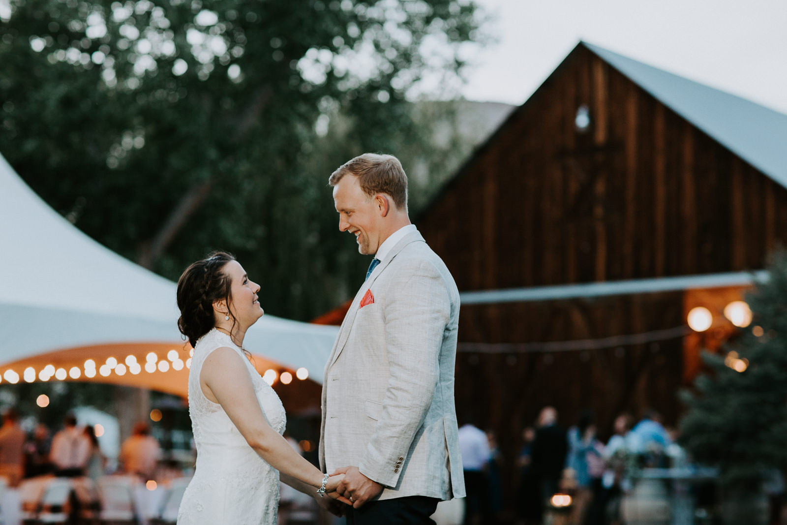 Wedding photograph of bride and groom holding hands facing each other with barn and tent in background