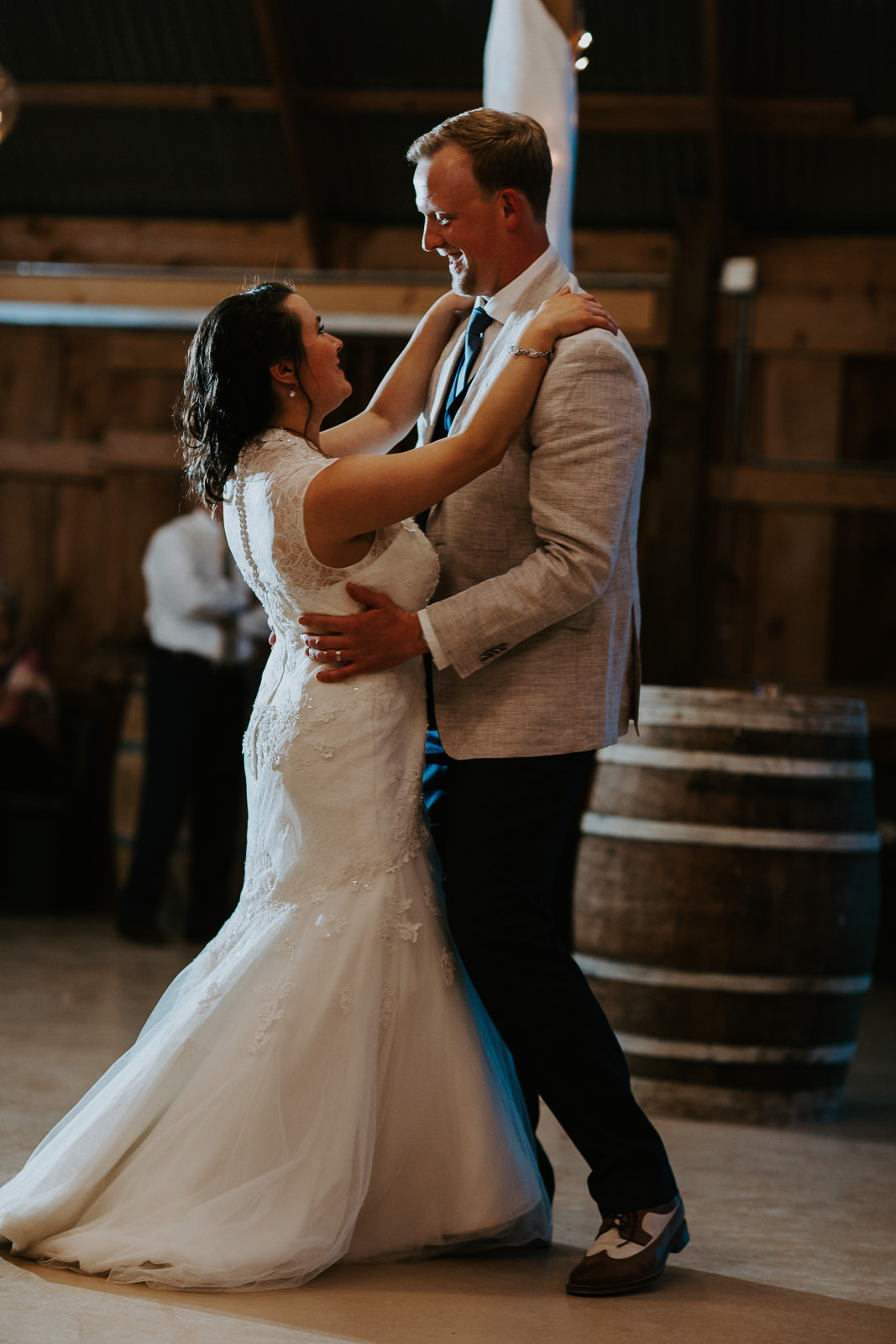 Portrait of bride and groom's first dance in barn with wine barrels