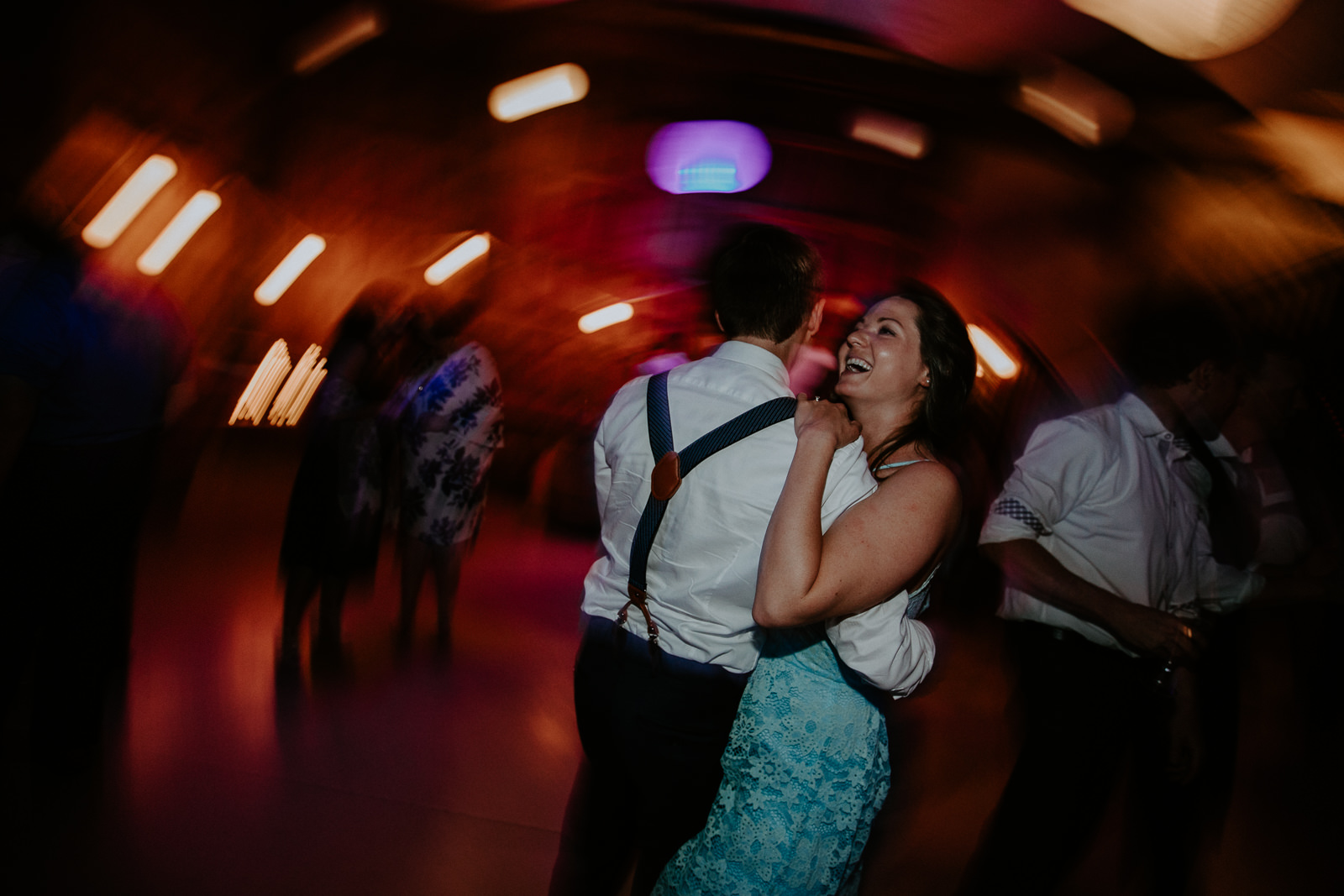 Two wedding guests dancing close with lights in background due to shutter drag