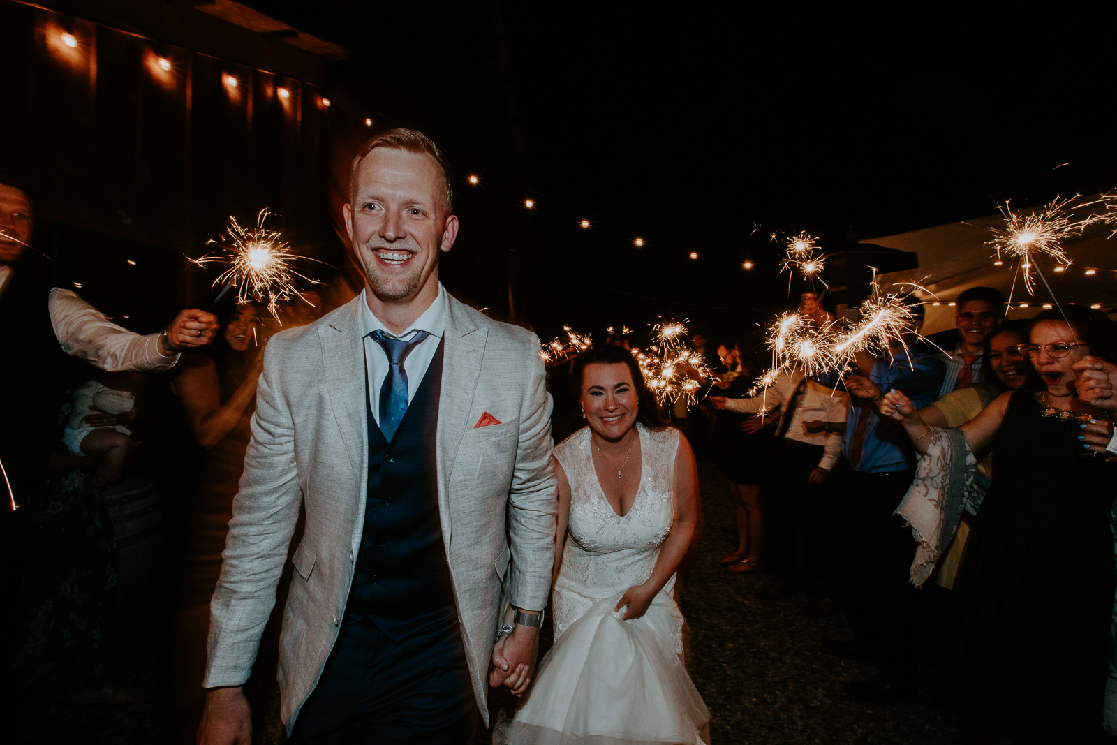 Wedding photo of sparkler exit of smiling bride and groom with guests on both sides in Palisade