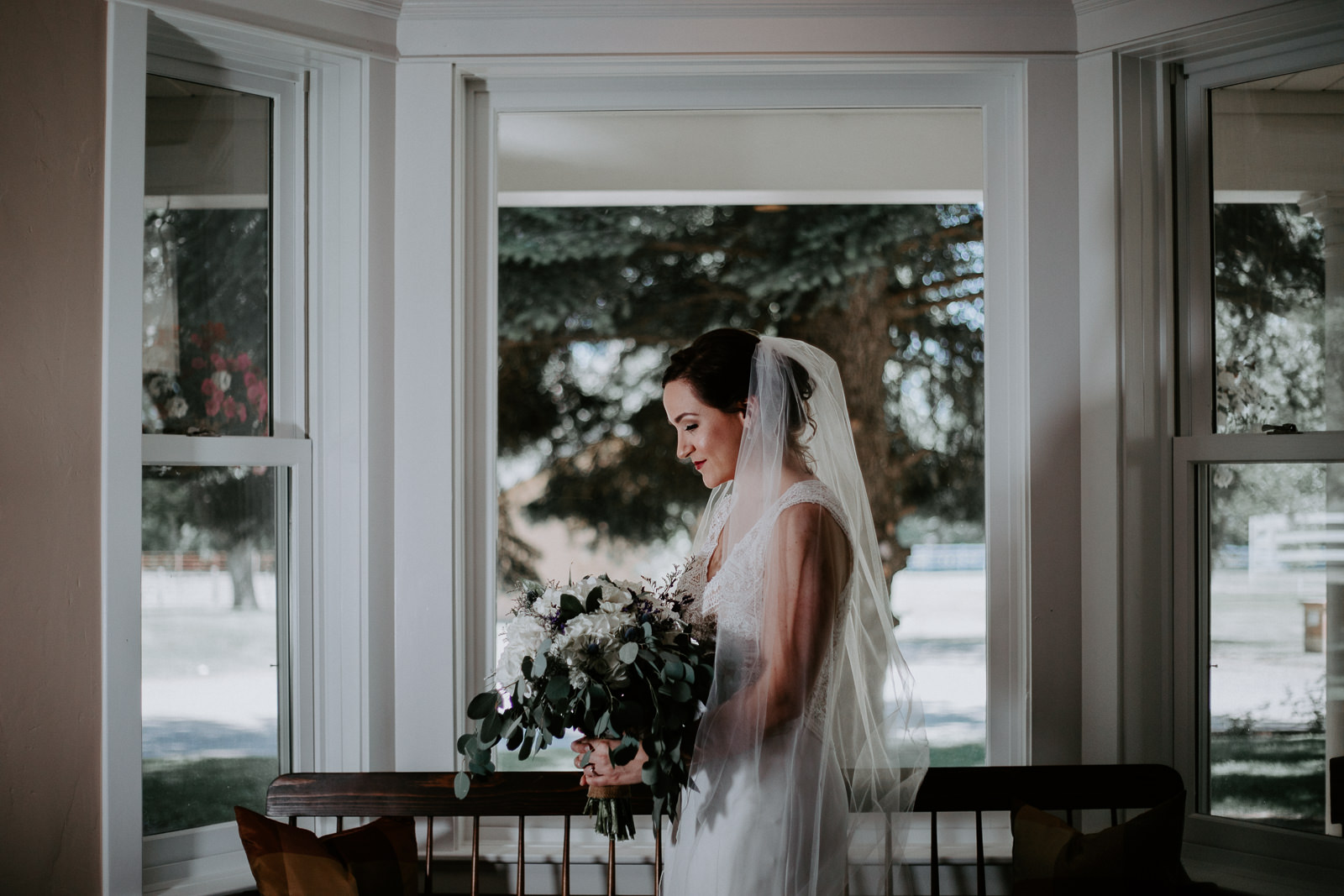 Bride with veil holding floral bouquet in front of windows in old farm house