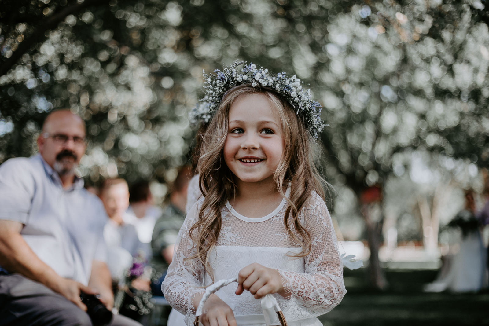 Flower girl smirking while walking down the aisle with guests behind her