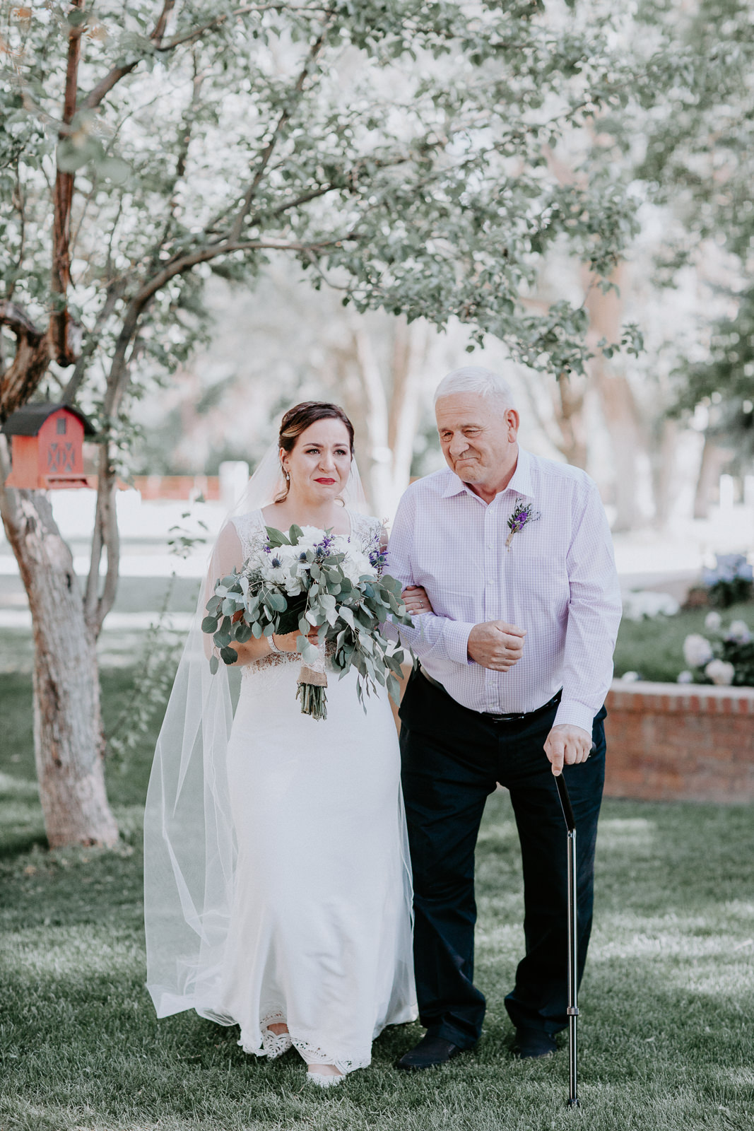 Father walking his crying daughter down the aisle during wedding ceremony