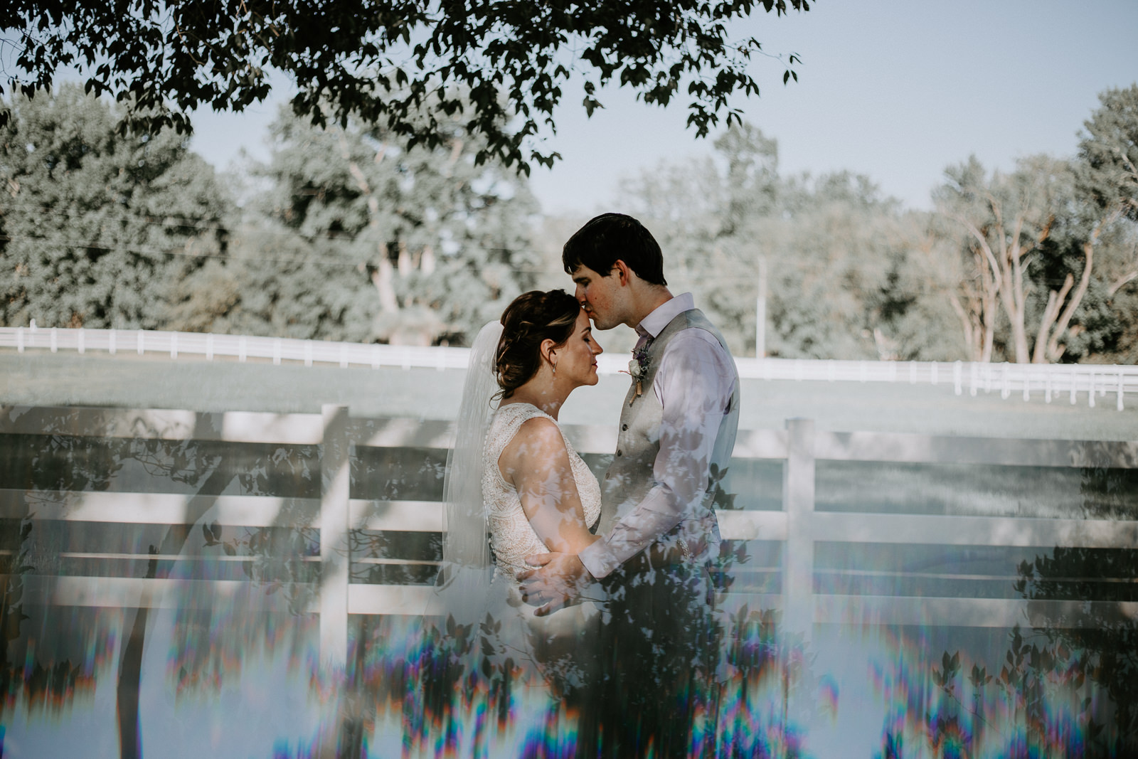 Groom kissing bride's head with prism reflection of trees