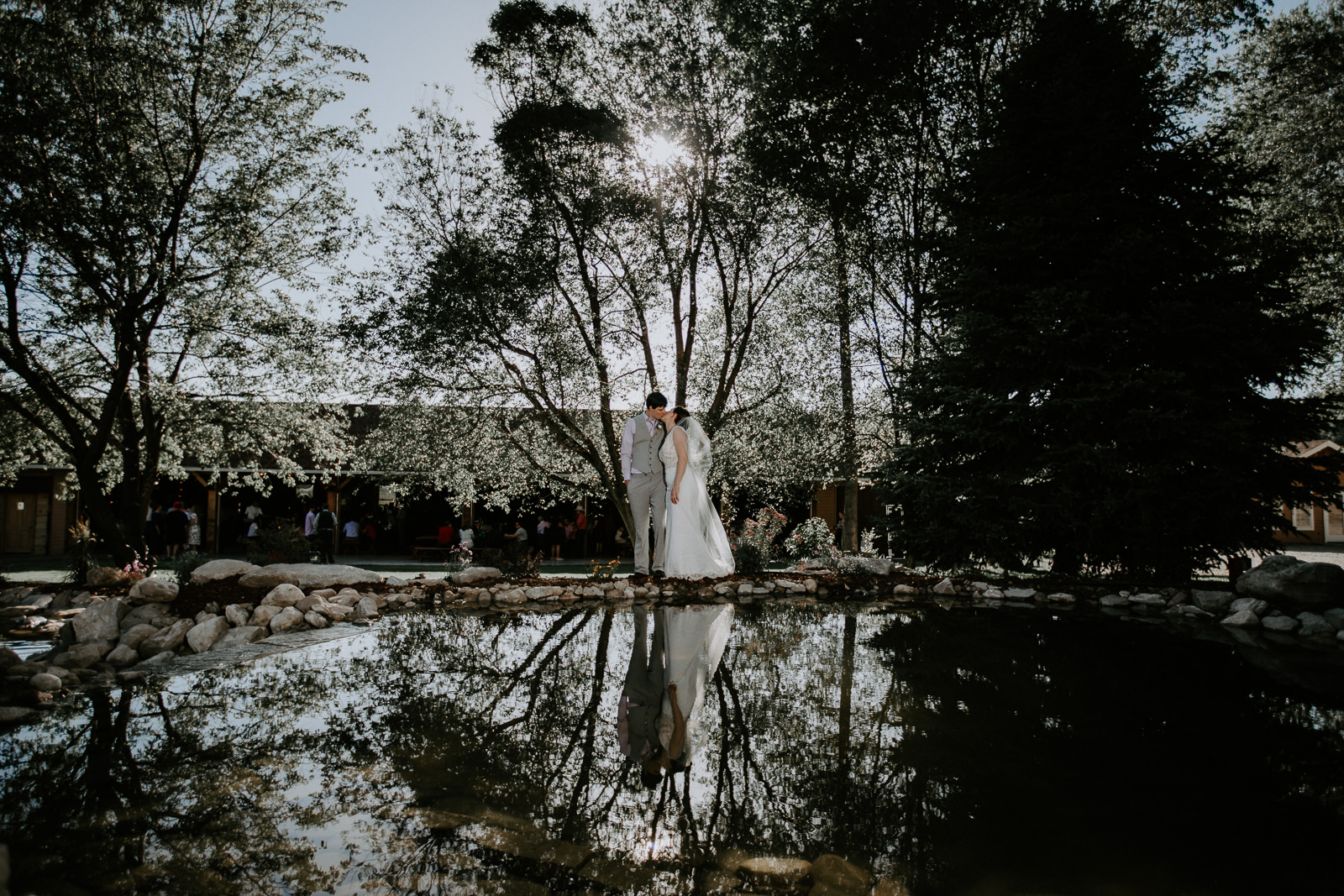Bride in white dress and groom in gray suit best with reflections
