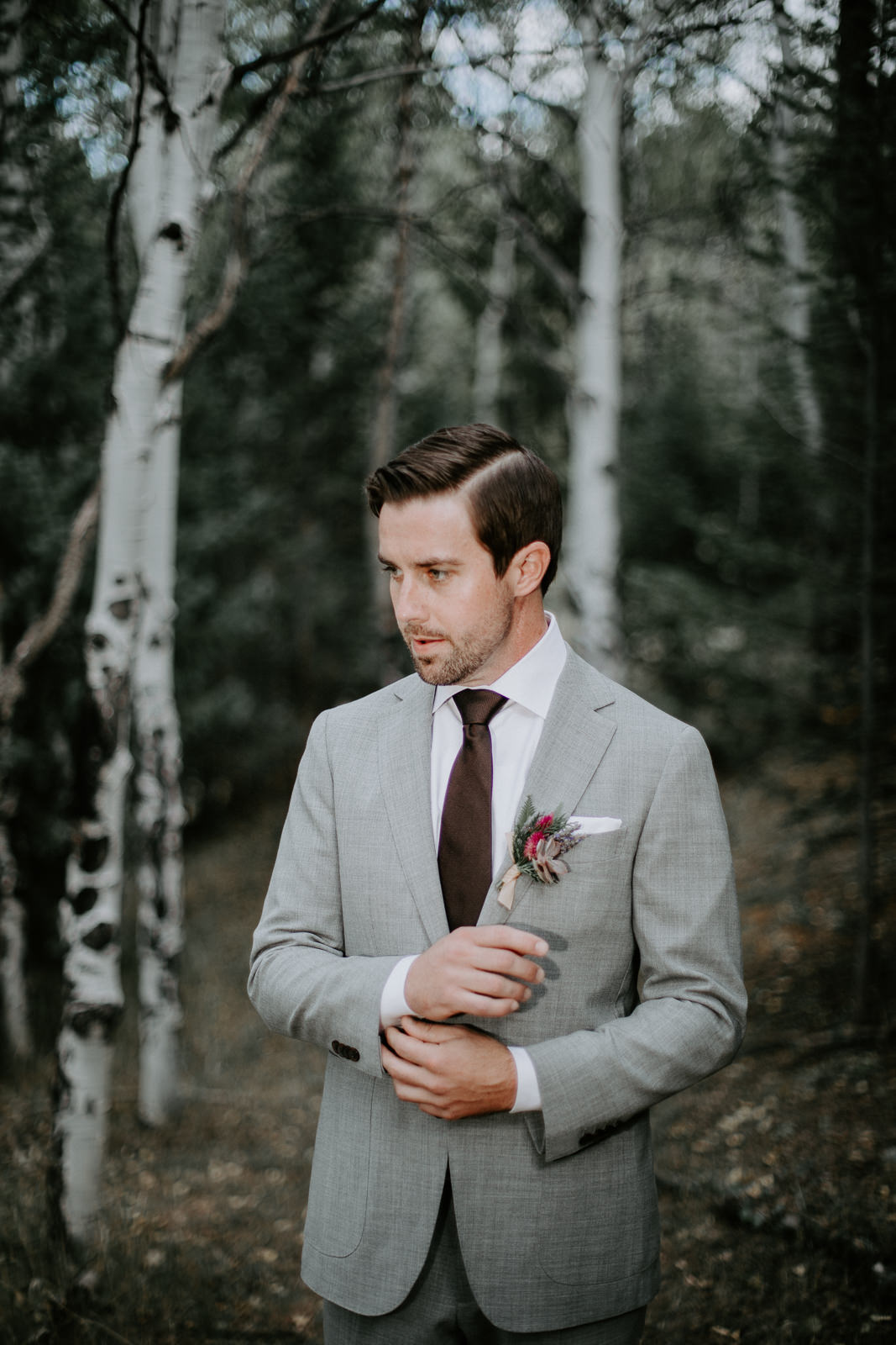 Groom in gray suit fixing cuffs among aspen trees waiting for his bride