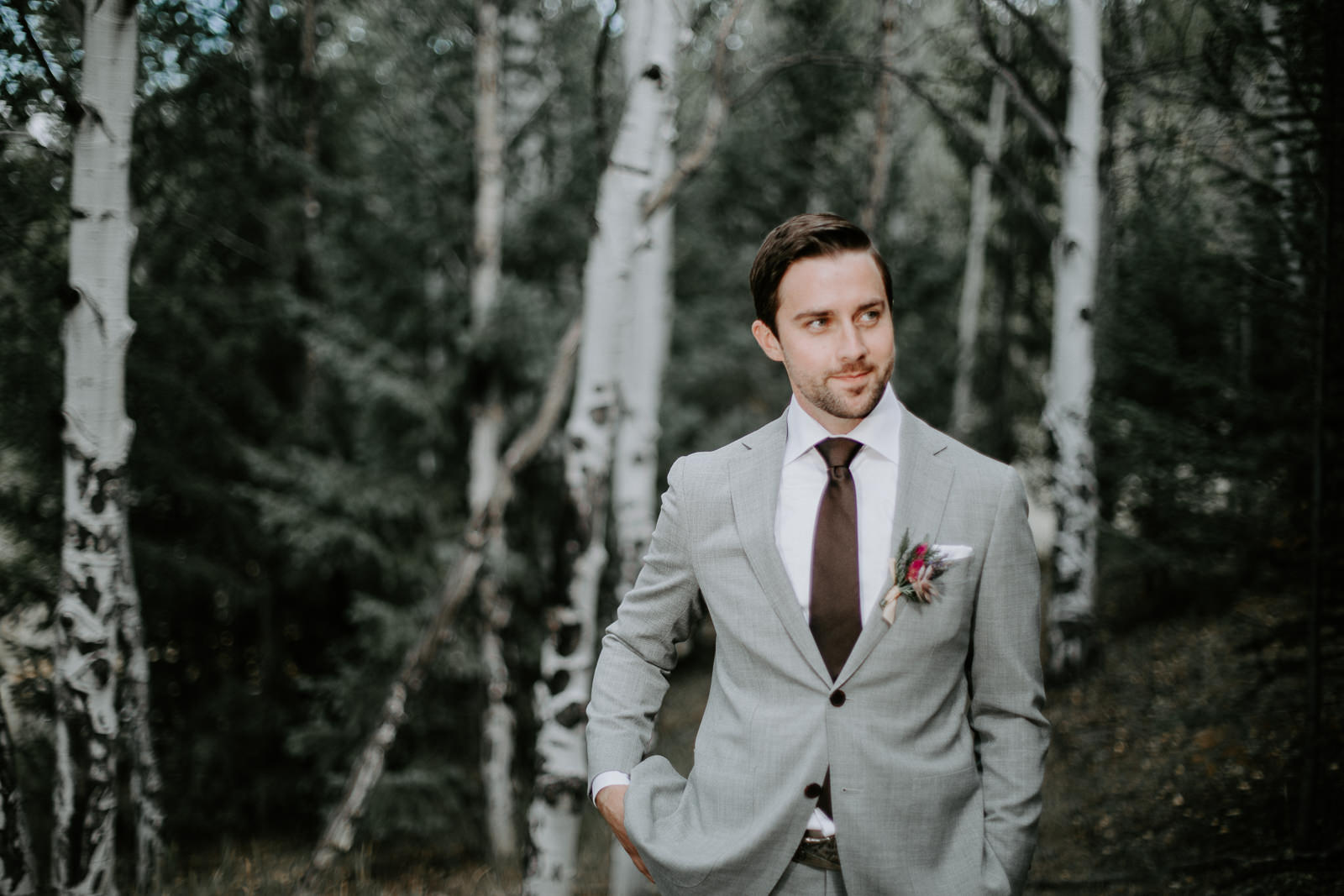 Smiling, anxious groom waiting for his bride during first look