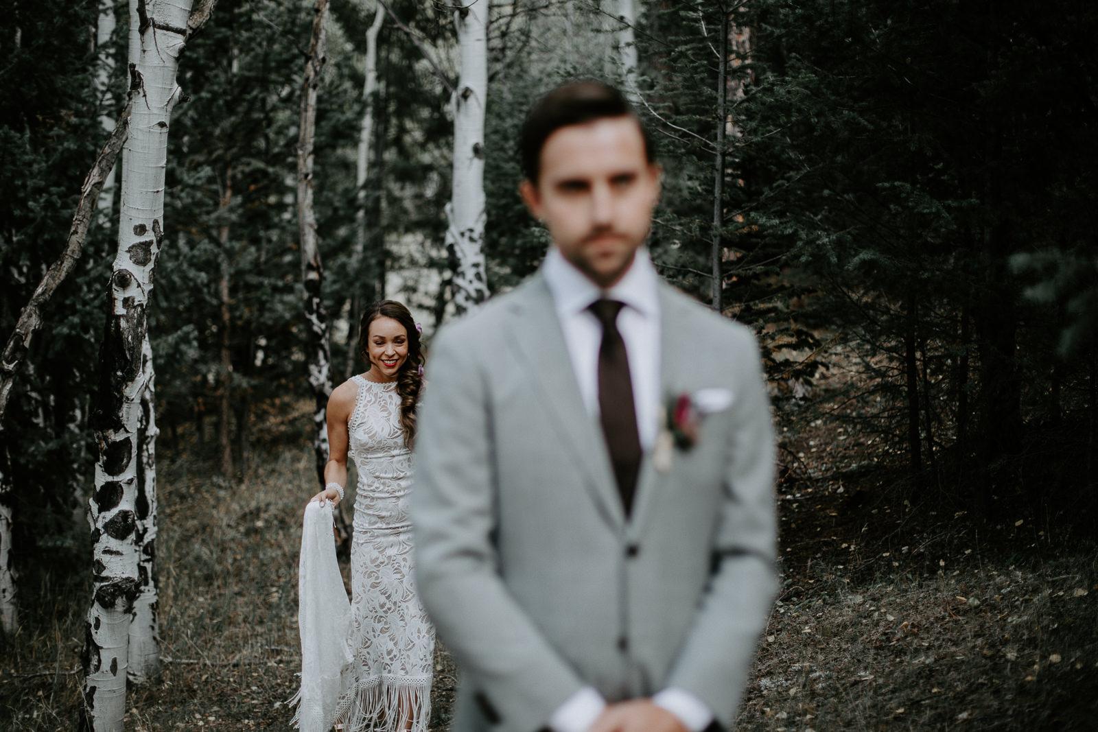 Bride in lacy white dress in focus behind groom blurred
