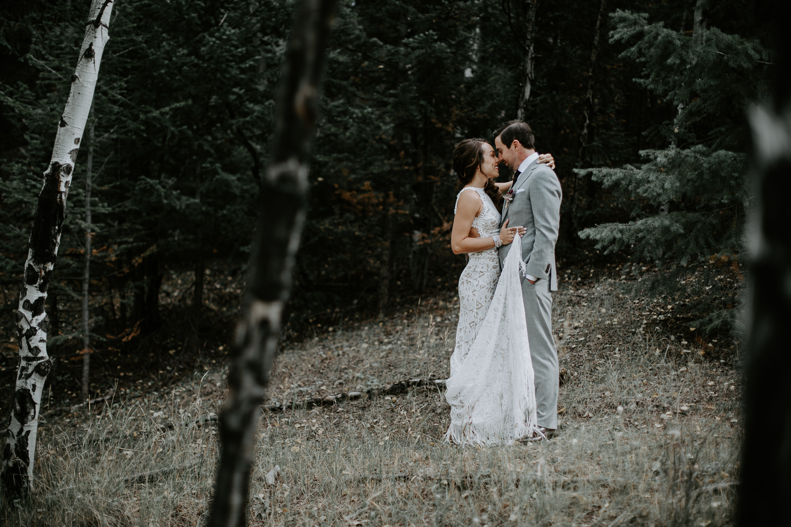 Embracing soon-to-be married couple standing among aspen trees