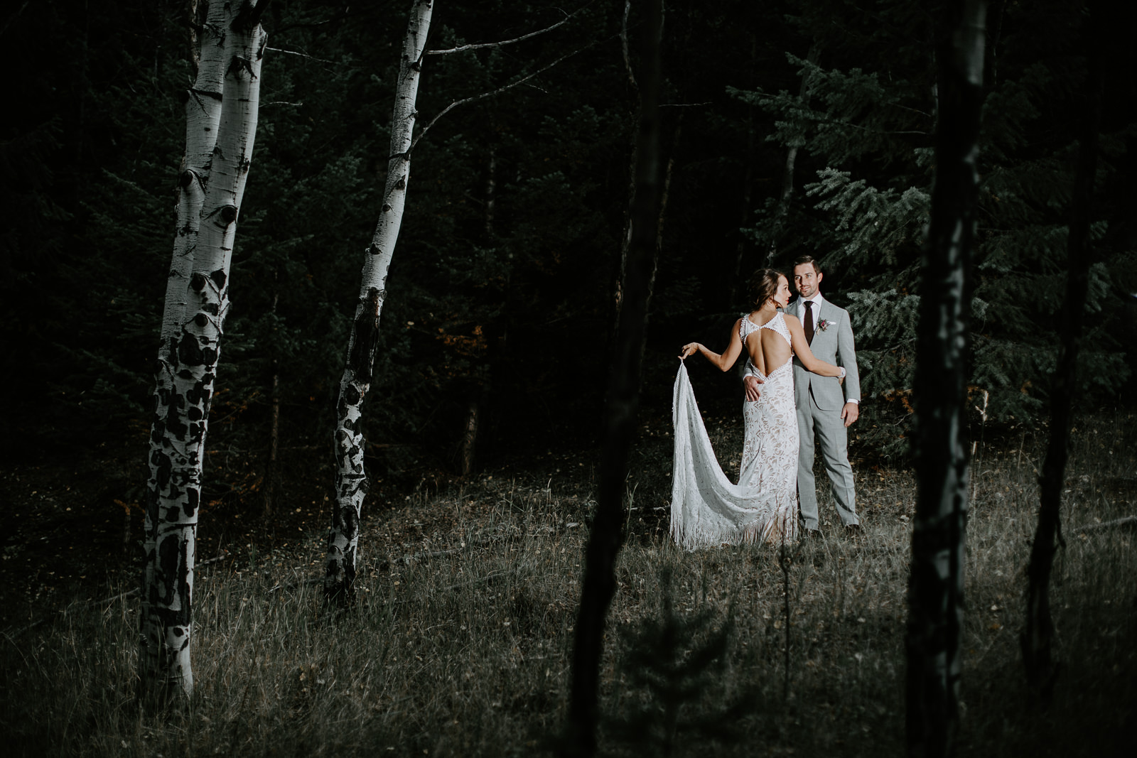 Bride holding white dress with groom illuminated amongst darkness and aspens