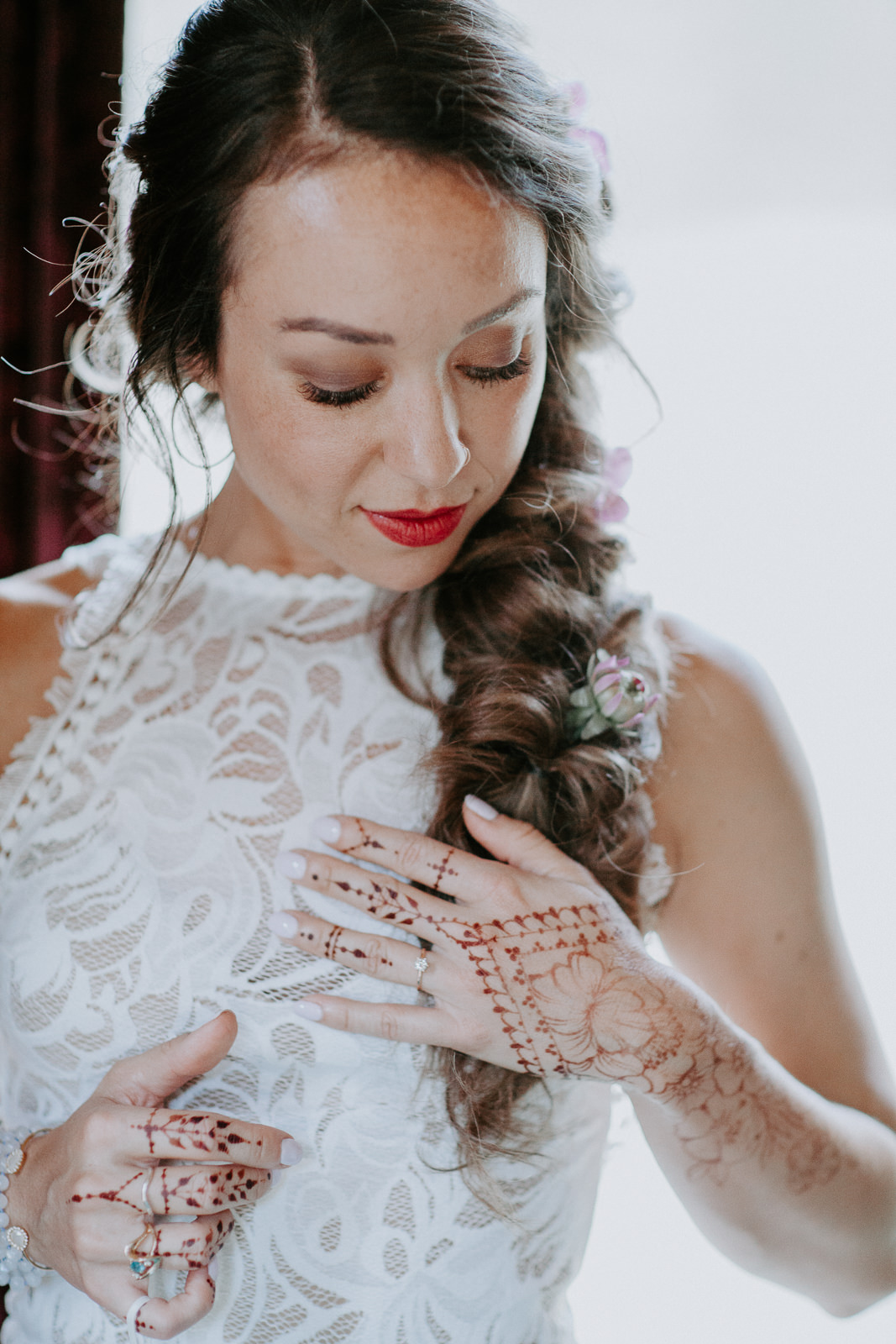Close up of bride in white dress showing her henna hands and arms