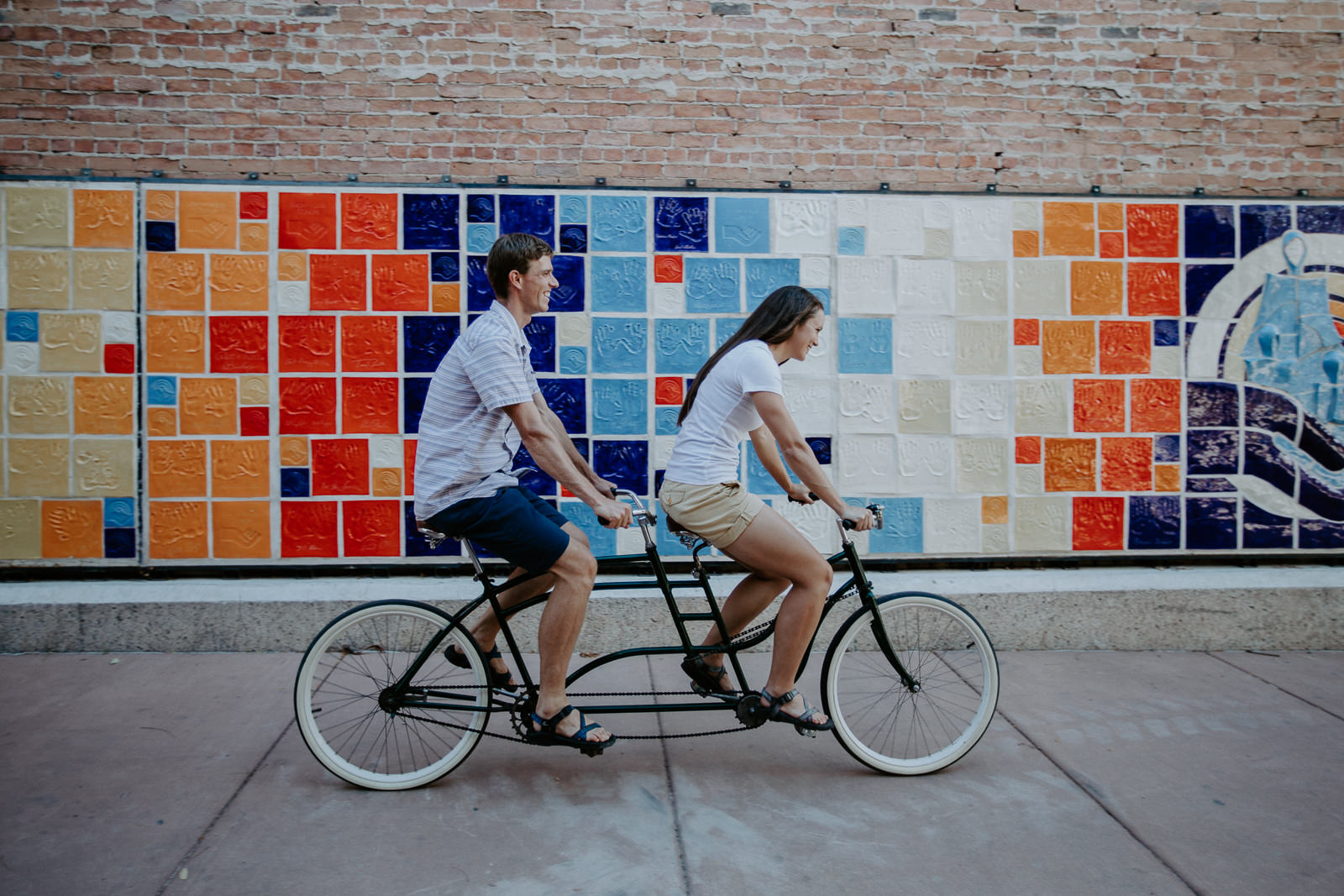Engaged couple riding a tandem bike laughing with colorful wall