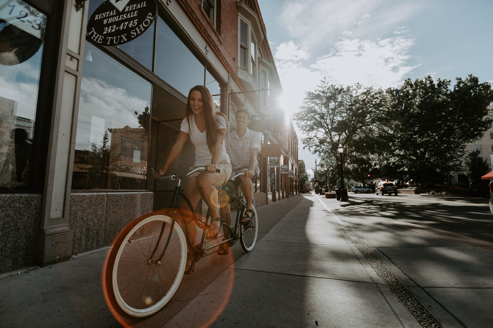 Sun behind couple riding tandem down Main Street
