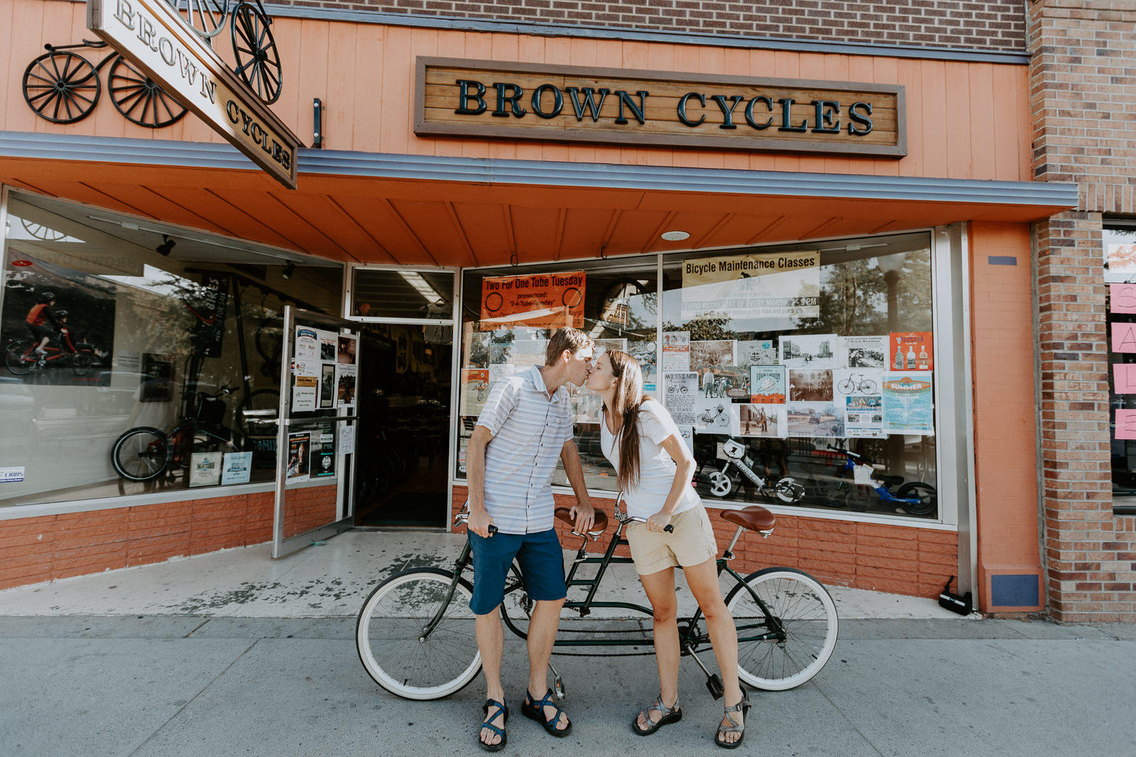 Couple leaning against bike while kissing in front of Brown Cycles