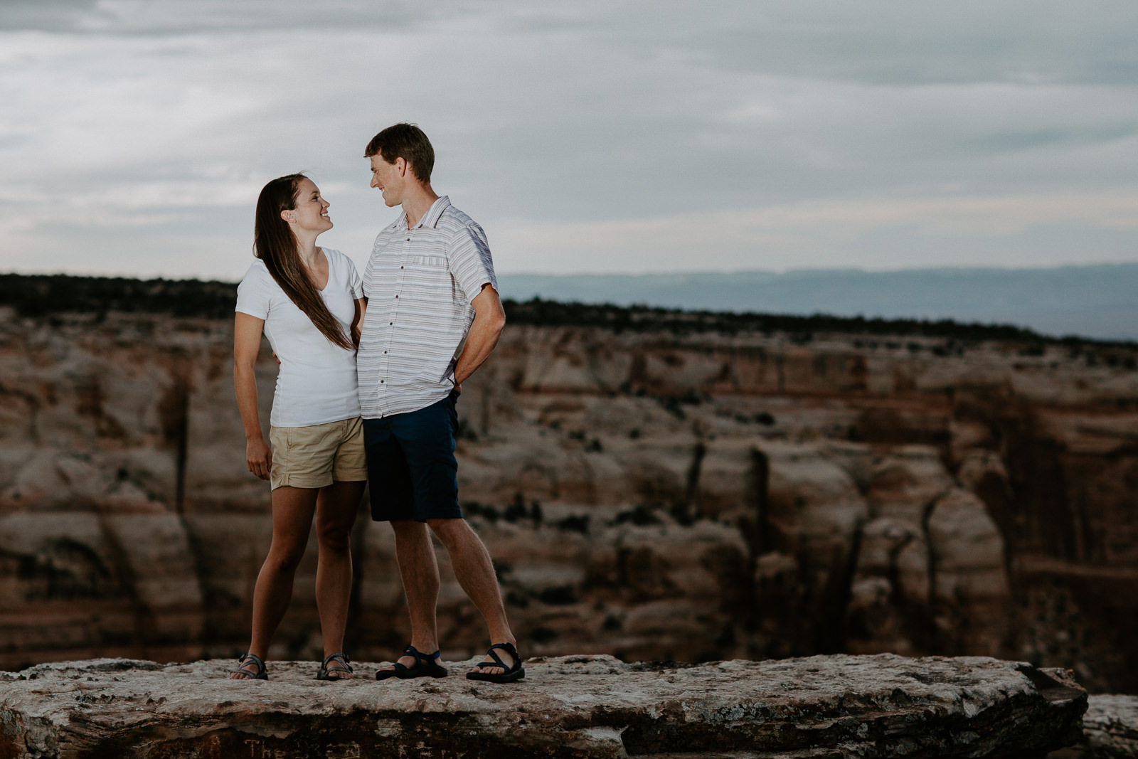 Couple smiling at each other with rock formations behind them in Grand Junction