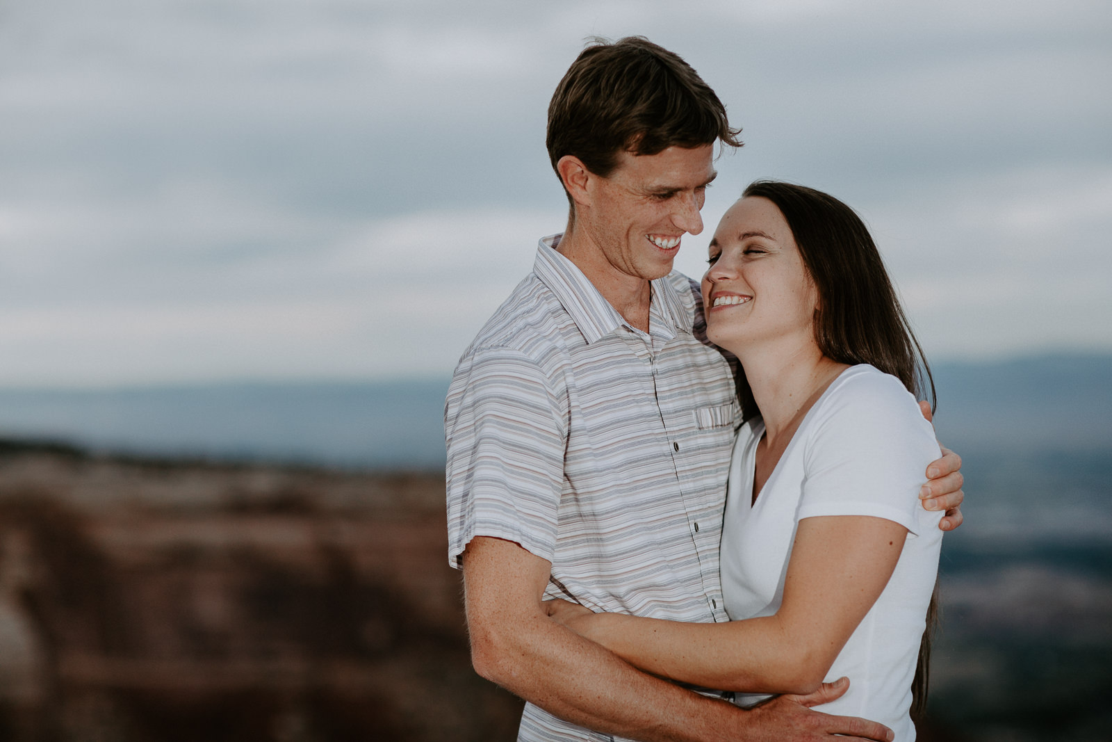 Closeup of engaged couple smiling and embracing with Bookcliffs of Grand Junction behind them