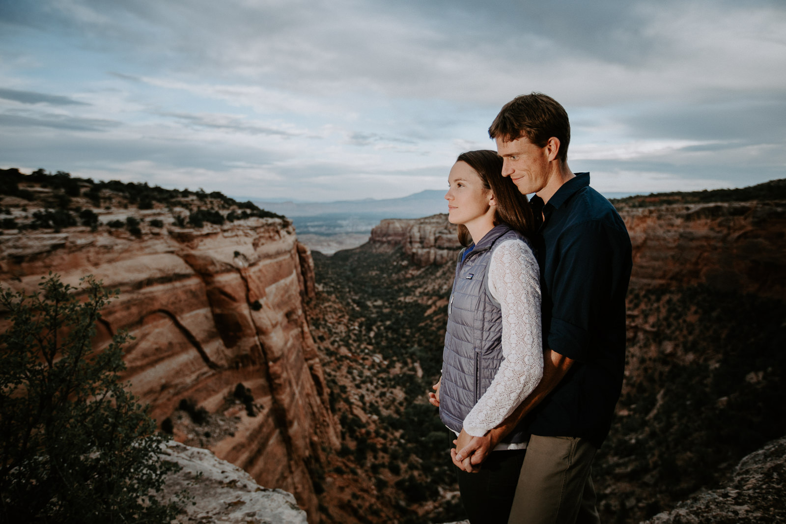 Candid moment of man holding his girlfriend from behind with cliffs desert canyon and town behind them