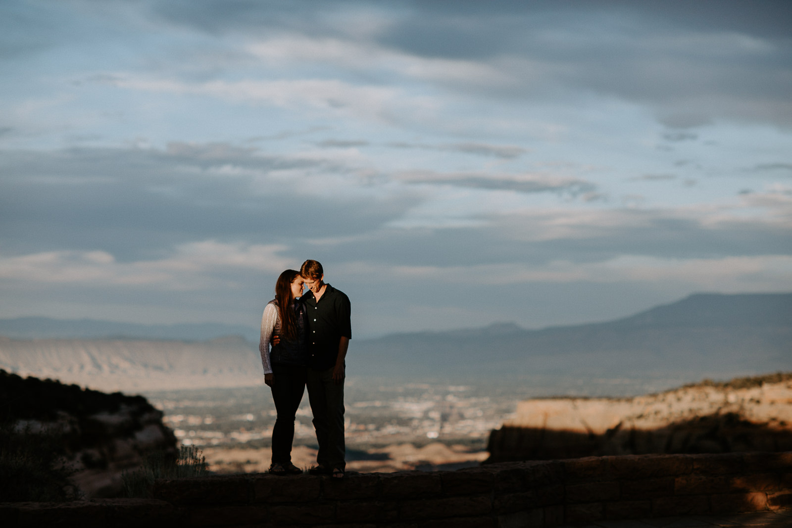 Authentic moment of man and woman silhoutted with faces illuminated by sun with Grand Mesa behind them