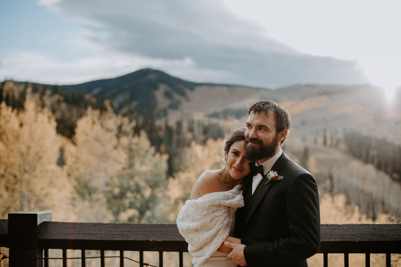 Bride and groom holding each other close overlooking yellow aspens and Beaver Creek