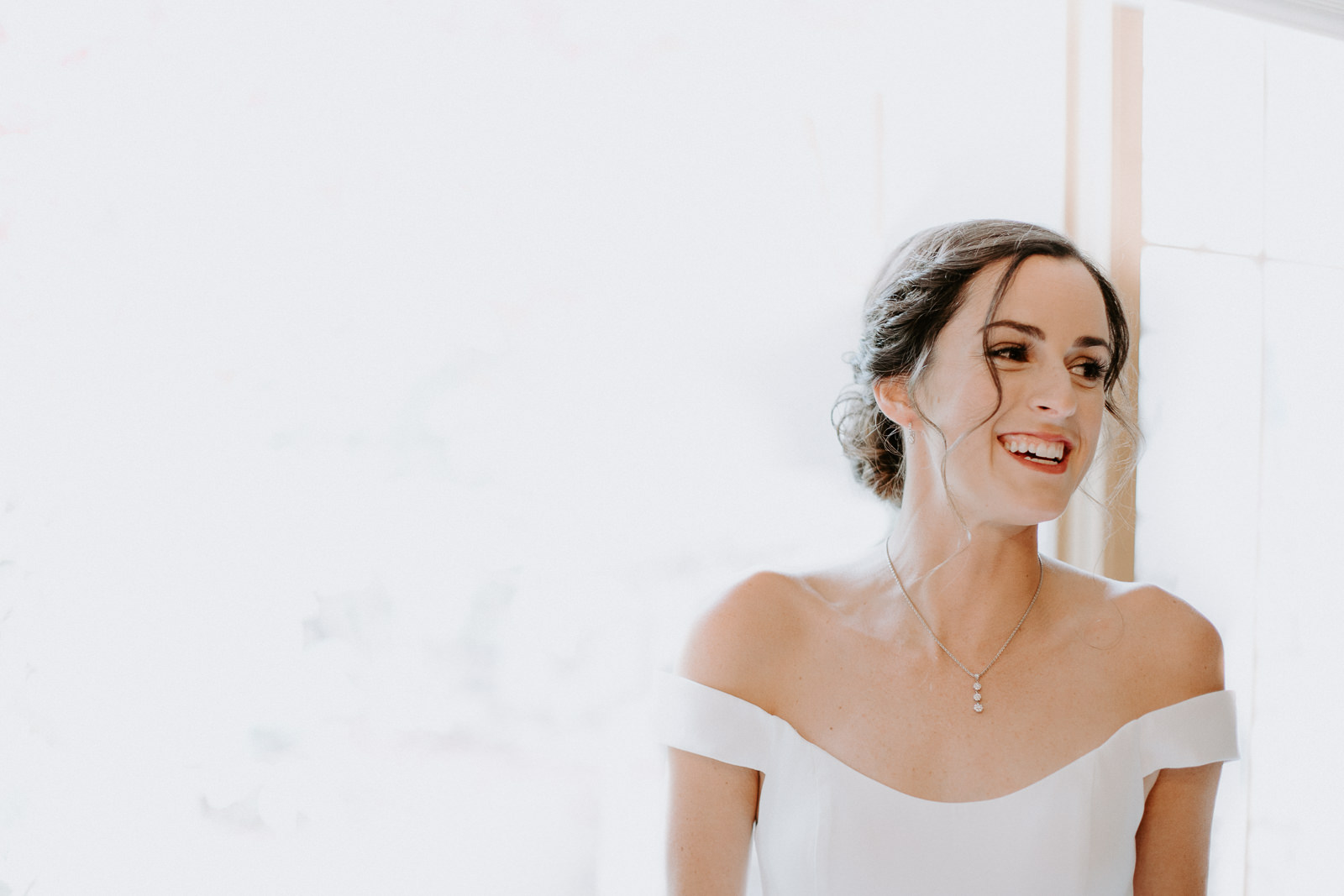 Bride laughing in a candid moment against white background