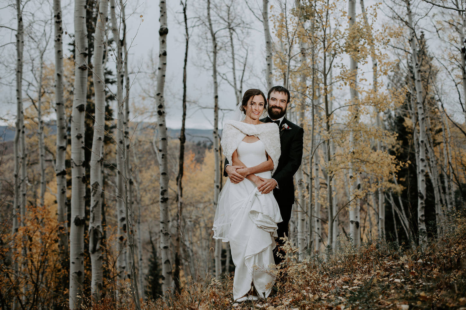Groom hugging his bride from behind among yellow and white aspen trees