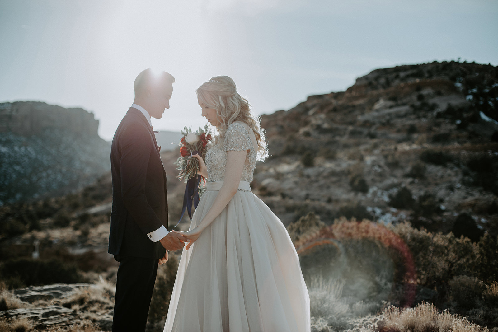 Bride and groom holding hands with sun behind them in Colorado National Monument