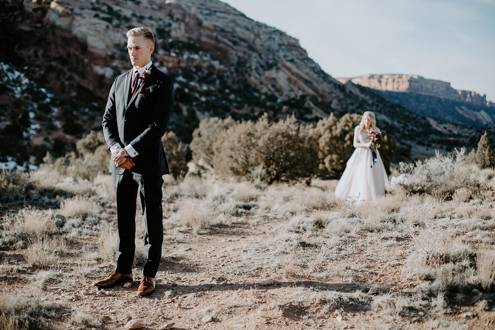 Groom standing in foreground while bride walks him behind during first look