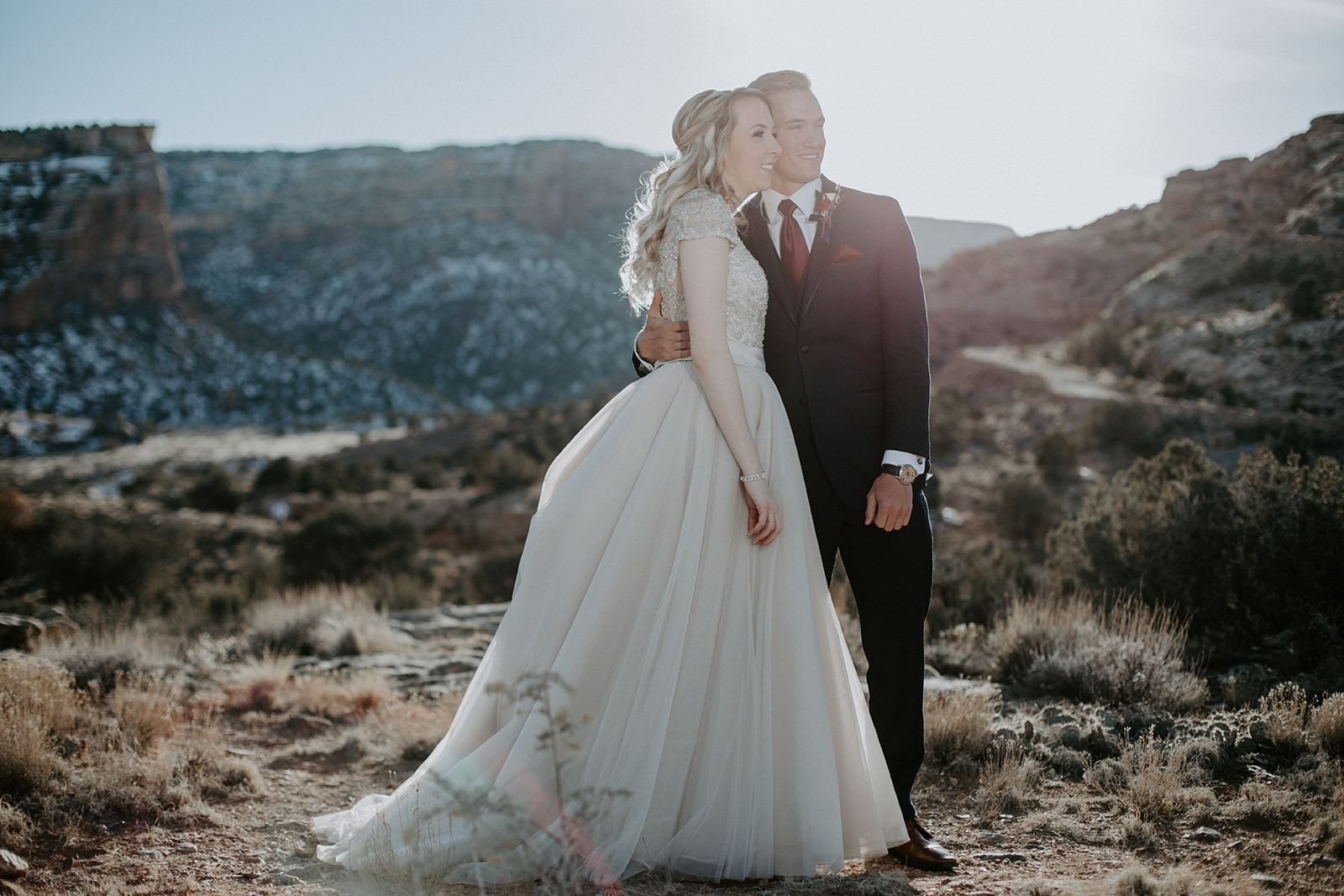 Hugging bride and groom looking away from camera in National Monument