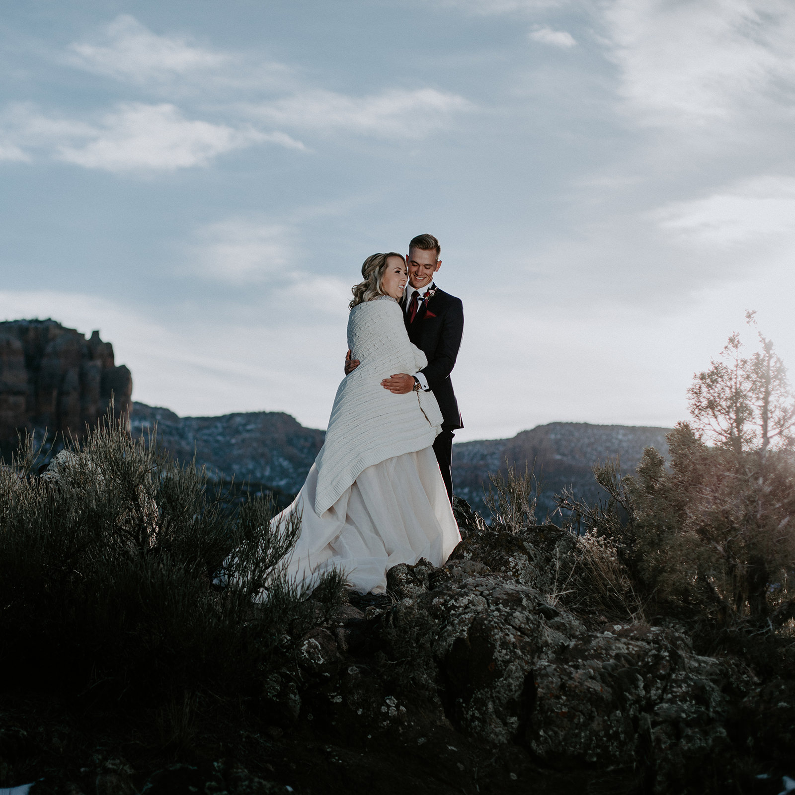 Wed couple holding each other on top of rocks